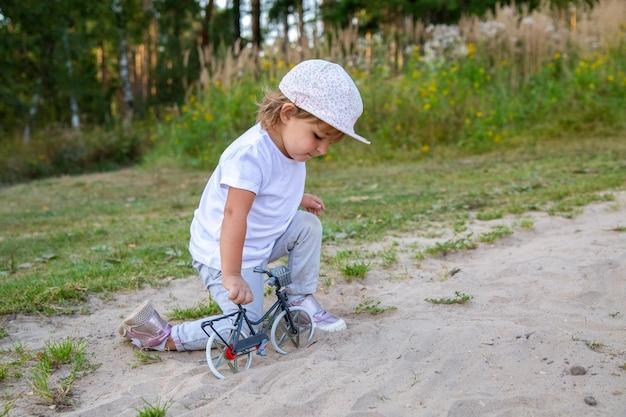 愛らしい幼児は芝生の砂の中で四つん這いで自然の子供でおもちゃの自転車で遊ぶ
