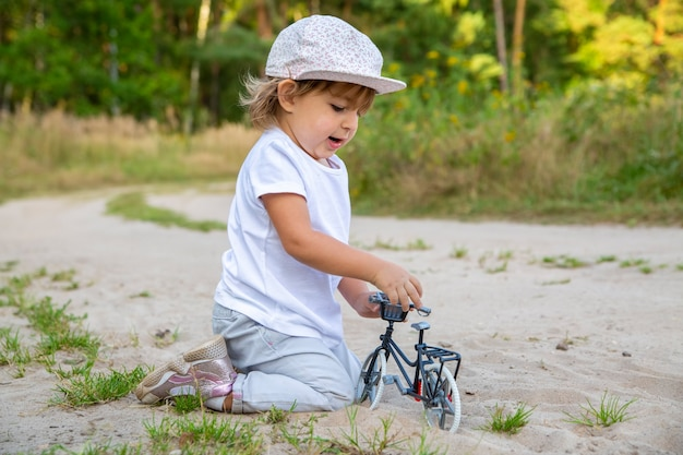 Adorable toddler plays with a toy bike in nature. child on all fours in the sand on the lawn.