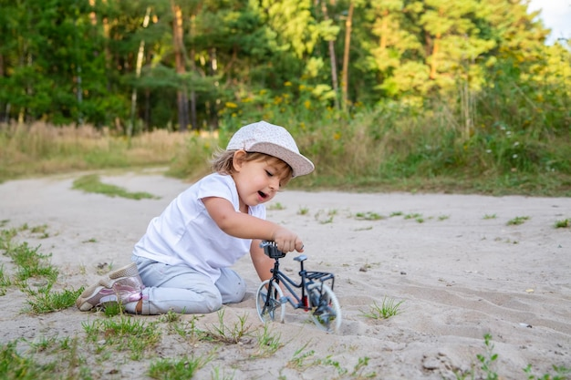 Adorable toddler plays with a toy bike in nature child on all fours in the sand on the lawn