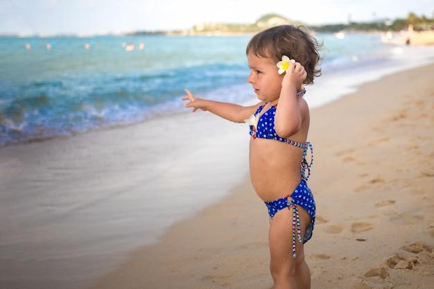 사랑스러운 유아 유아는 모래 해변에 서서 열대 바다를 가리킵니다.