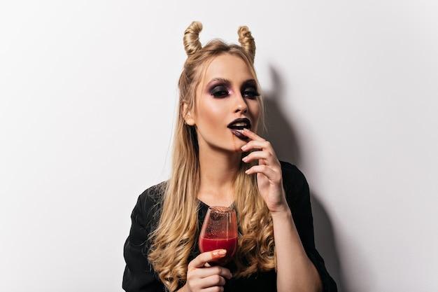 할로윈에 포즈를 취하는 사랑스러운 뱀파이어 소녀. 피를 마시는 검은 화장과 관능적 인 여자의 실내 사진.