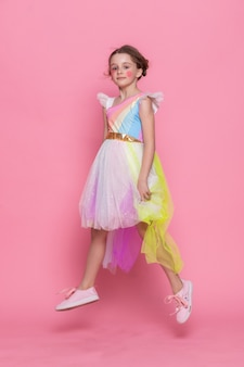 Adorable view of happy little girl wearing unicorn headband with pink wall as background. portrait of cute smiling child with unicorn horn and ears standing on the sidewalk. lovely kids in costumes