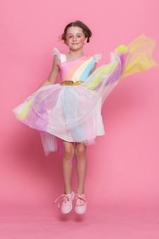 분홍색 벽을 배경으로 유니콘 머리띠를 한 행복한 어린 소녀의 사랑스러운 전망. 유니콘 뿔과 귀가 보도에 서 있는 귀여운 웃는 아이의 초상화. 의상을 입은 사랑스러운 아이들