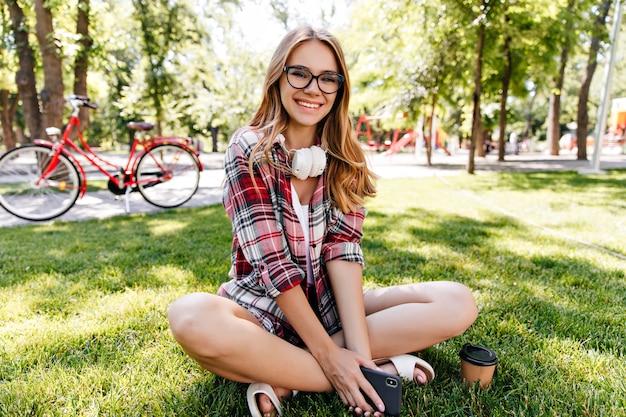 Прелестная белая девушка в повседневной одежде, сидя на земле с улыбкой. наружное фото эффектной дамы со светлыми волосами, наслаждающейся выходными.