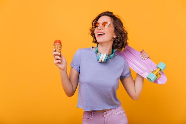 Прелестная белая девушка с мороженым, выражая счастье. крытый портрет эффектной дамы с симпатичным фиолетовым скейтбордом.