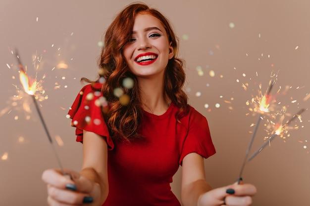 벵골 빛과 함께 포즈를 취하는 사랑스러운 백인 여자. 폭죽을 들고 새 해에 웃 고 화려한 red-haired 소녀.
