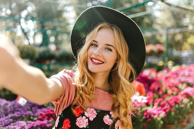 花と温室で自分の写真を撮る愛らしい白人女性。オレンジリーで自分撮りをする楽しい女性を笑う。