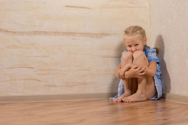 Прелестная белая маленькая девочка, сидящая в углу дома, изолированном на деревянных стенах.