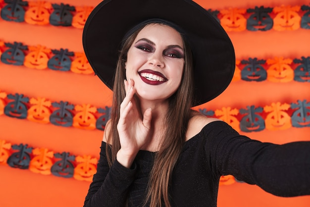 Adorable witch girl in black halloween costume smiling at camera isolated over orange pumpkin wall
