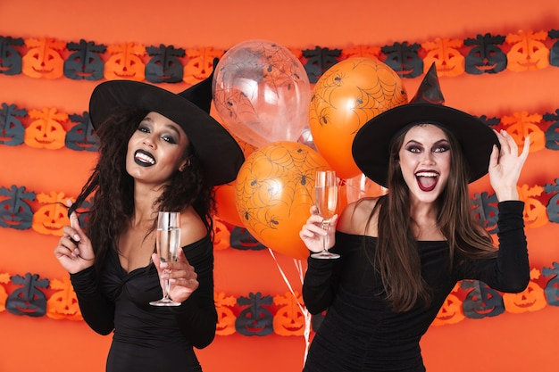 Adorable witch women in black halloween costume drinking champagne isolated over orange pumpkin wall