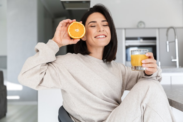 Adorable woman 30s drinking orange juice, while resting in bright modern room