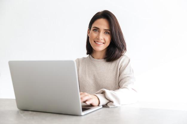 Очаровательная женщина 30 лет работает на ноутбуке, сидя на белой стене в светлой комнате