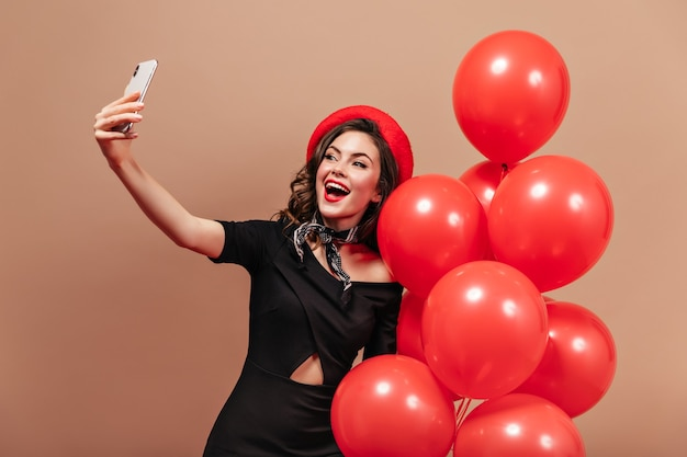 Adorable woman in black dress and red beret is holding smartphone, making selfie and posing with balloons.