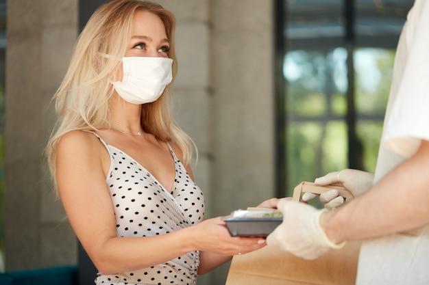 Очаровательная женщина-покупательница принимает заказ в ресторане во время коронавируса