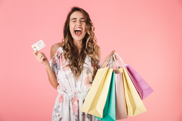 Adorable woman in dress holding credit card and colorful shopping bags, isolated on pink