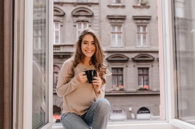 ラテのカップで敷居にポーズをとっている間、前向きな感情を表現する愛らしい女性