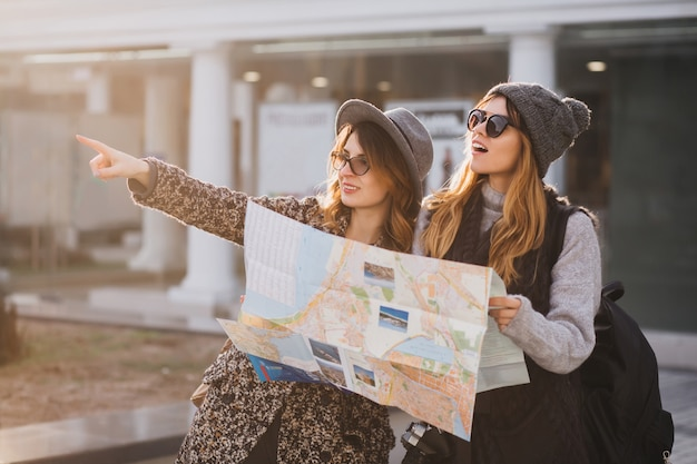 Adorable woman in gray knitted hat walking with friend around city and holding map. outdoor portrait of two charming female travelers looking at something inetersting in distance and pointing finger.