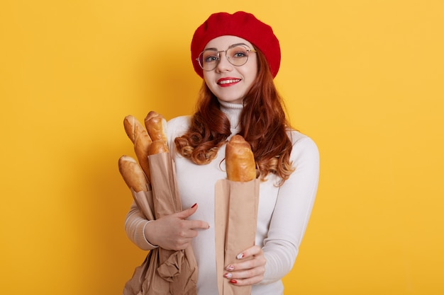Adorable woman holding paper bag with long bread baguettes, offers one to somebody, wearing white shirt, red beret and glasses on yellow