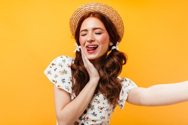 Очаровательная женщина в канотье и с бантами на волосах показывает язык и делает селфи на оранжевом фоне.