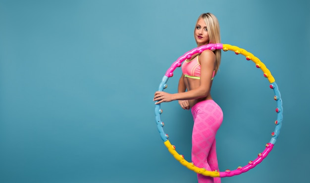 Очаровательная женщина в розовой спортивной одежде позирует с обручем