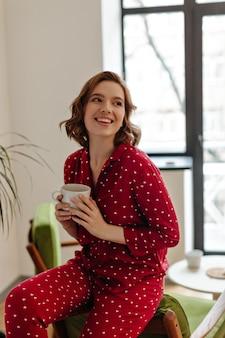 一杯のコーヒーを保持している赤いパジャマの愛らしい女性。家でお茶を楽しんでいる笑顔の若い女性の屋内ショット。