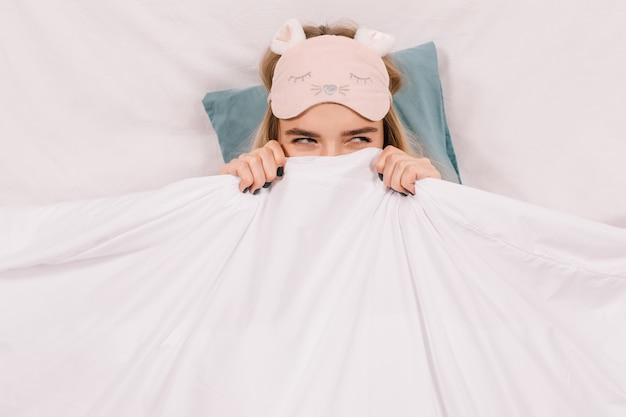 Очаровательная женщина в маске сна позирует в постели