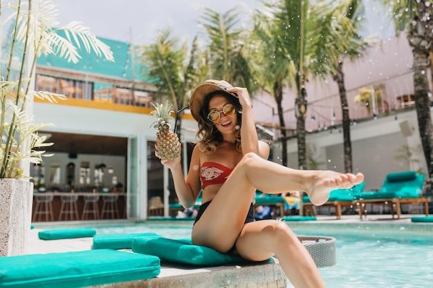 수영장에서 장난스럽게 포즈를 취하는 선글라스에 사랑스러운 여자. 이국적인 리조트에서 파인애플 칵테일을 마시는 모자에 매력적인 곱슬 여자의 야외 샷.