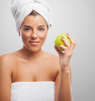 リンゴで頭に白いタオルで愛らしい女性