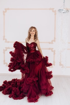 Adorable woman in red burgundi dress poses in a bright luxury room with large chandelier