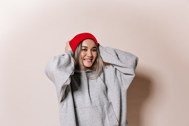 Adorable woman in red cap and sweatshirt smiling on isolated wall