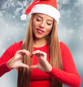 Adorable woman showing a heart