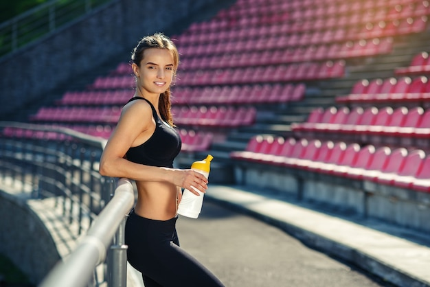 Adorable woman on the stadium tribune after training with the bottle of water in her hand