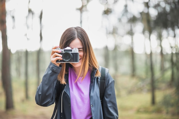 Adorable woman taking photos in forest