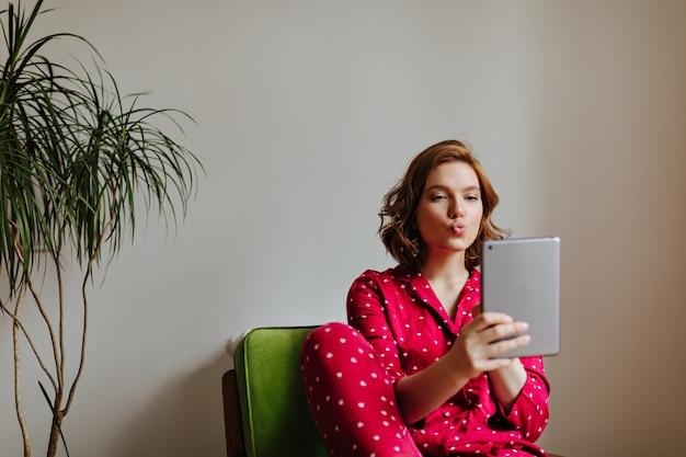 Очаровательная женщина, делающая селфи с выражением лица поцелуи. крытый снимок фигурной женщины в пижаме с помощью цифрового планшета.