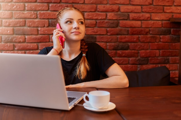ノートパソコンを介してオンラインで作業しながらカフェでスマートフォンで話している愛らしい女性