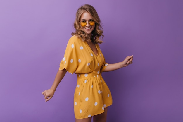 Donna adorabile in abbigliamento arancione dell'annata che ride alla macchina fotografica. ritratto di una ragazza spettacolare con ragazza bionda ondulata isolata su viola.