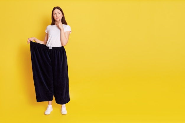 Adorable woman wearing big size pants standing with thoughtful facial expression, keeping finger on lip, looking away, copy space for promotion,isolated over yellow wall.