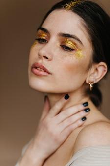 Donna adorabile con capelli neri che posano sulla parete marrone. incredibile modello femminile con trucco dorato in piedi con gli occhi chiusi.