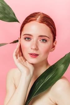 분홍색 배경에 포즈 녹색 잎을 가진 사랑스러운 여자. 카메라를보고 잠겨있는 생강 소녀의 스튜디오 샷.