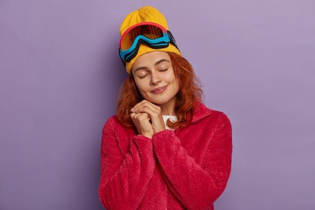 Очаровательная женщина с рыжими волосами, наслаждается зимним сезоном, наклоняет голову и закрывает глаза, носит теплую красную куртку, позирует над фиолетовой стеной.