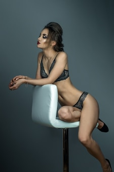 Adorable woman with red lips and beautiful hairstyle sits on white leather chair in grey lace underwear in studio
