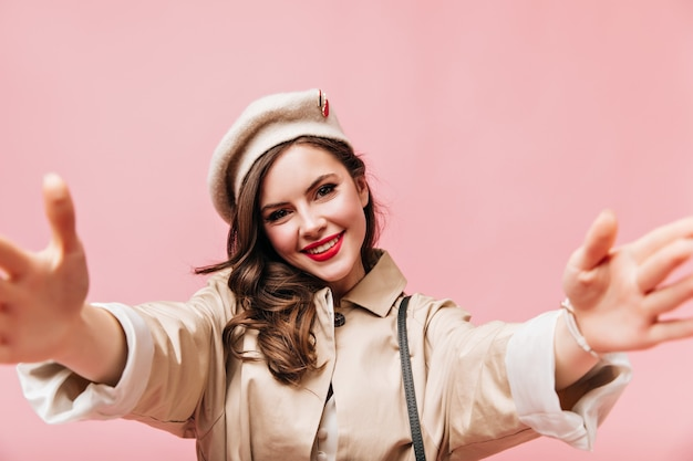 Adorable woman with red lipstick makes selfie. portrait of girl in beige autumn outfit on pink background.