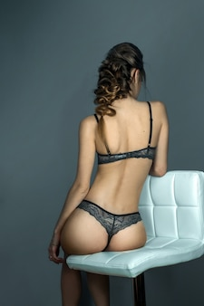 Adorable woman with sexual round buttocks sits on white leather chair in grey lace underwear in studio
