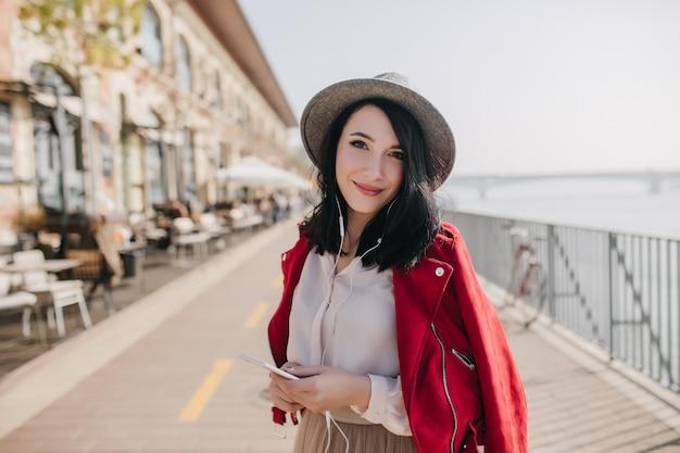 Очаровательная женщина с прямыми короткими волосами слушает музыку на набережной в солнечный день