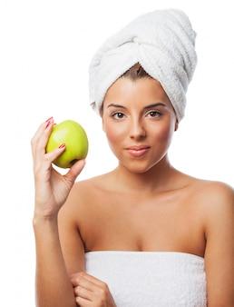 Donna adorabile con asciugamano avvolto sulla testa che tiene mela
