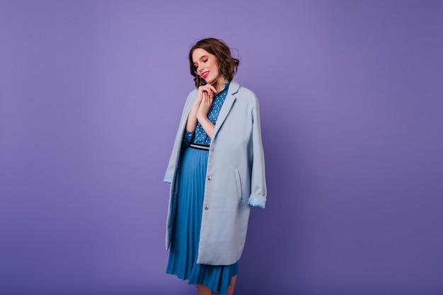 Adorabile donna con trucco alla moda guardando verso il basso durante il servizio fotografico. allegra ragazza riccia in cappotto blu.