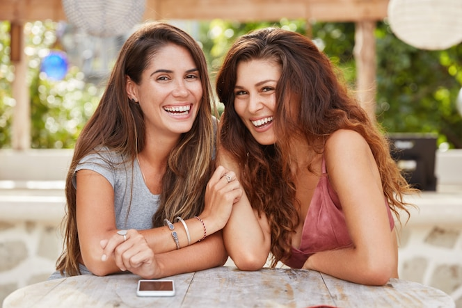 Adorable women have pleased expressions, sit close to each other, wait for order in cafeteria.