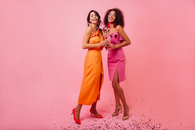 Очаровательные женщины в длинном оранжевом платье наслаждаются съемкой
