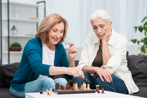 Adorable women playing chess together