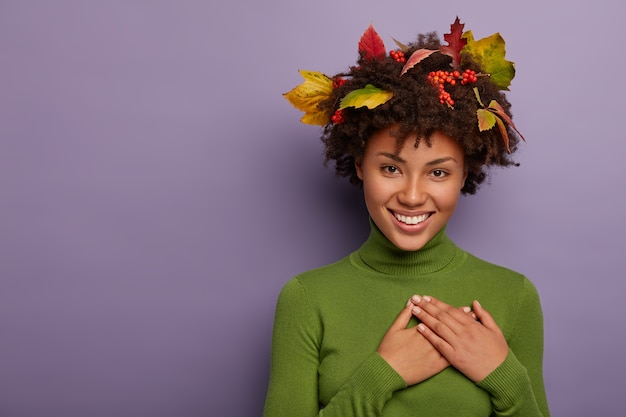 Adorable young afro american lady feels gratitude, has hands folded on chest, weras long sleeved green jumper, leaves on curly hair